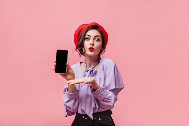 Jong meisje met groene ogen toont smartphone op roze achtergrond. portret van dame in rode hoed en lila blouse met franje.
