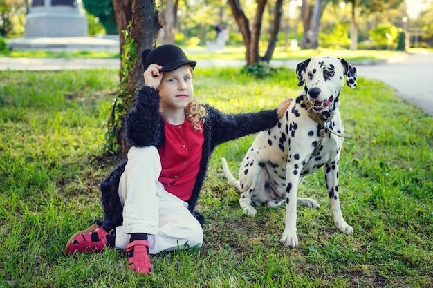 Jong meisje met haar dalmatische honden in een de lentepark.