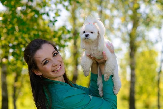 Jong meisje met haar hond. puppy witte hond loopt met zijn eigenaar. conceptie over vriendschap, dier en vrijheid.
