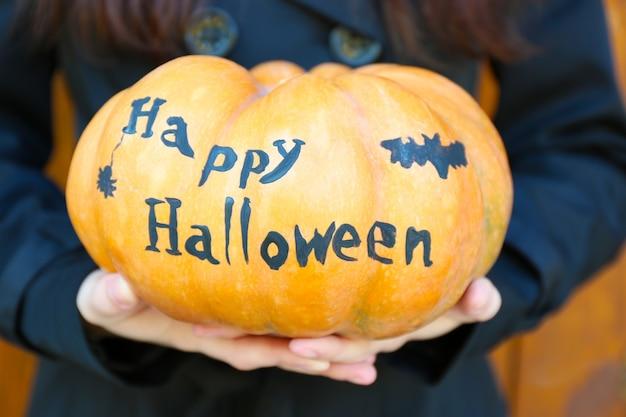 Jong meisje met halloween-pompoen, close-up, buitenshuis