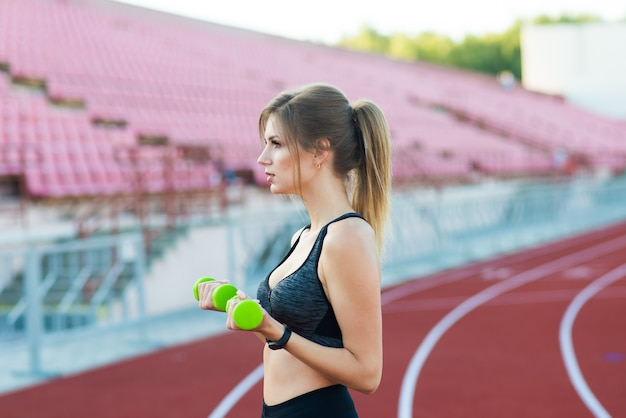 Jong meisje met halters in handen op stadion. sport en gezond concept.