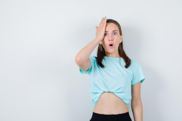 Jong meisje met hand op hoofd in turquoise t-shirt, broek en verbaasd, vooraanzicht.