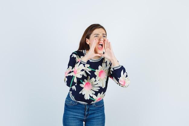 Jong meisje met handen in de buurt van mond als iemand bellen in bloementrui, jeans en schreeuwen, vooraanzicht.