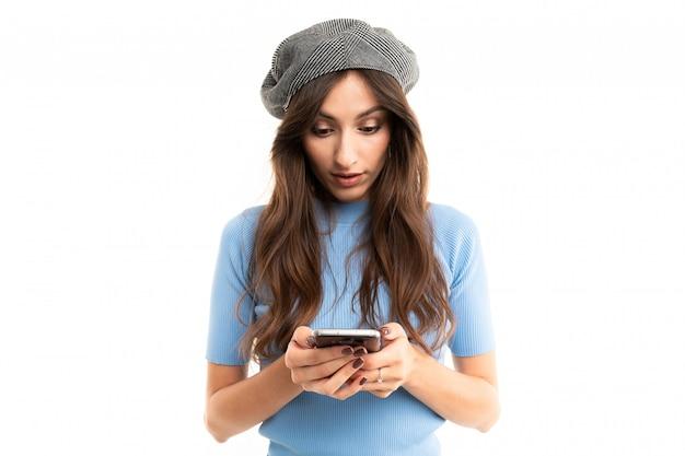 Jong meisje met heerlijke glimlach, lang golvend kastanjehaar, mooie make-up, in blauwe trui, zwarte jeans, grijze baret, met rode armbandstandaards met telefoon in de hand