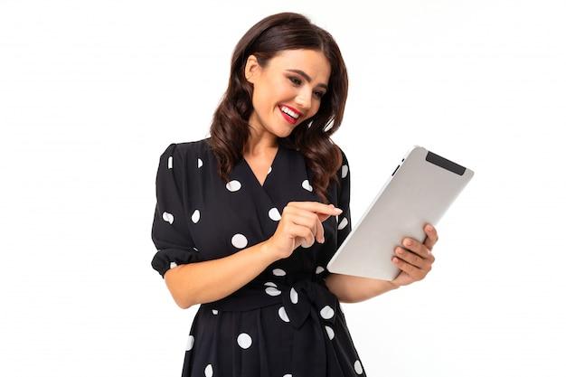 Jong meisje met heerlijke glimlach, platte tanden, rode lippenstift, lang golvend kastanjebruin haar, mooie make-up, in zwart-witte jurk in erwten houdt een tablet