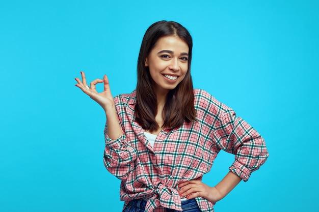 Jong meisje met heldere glimlach die casual overhemd dragen en ok gebaar over blauwe muur tonen