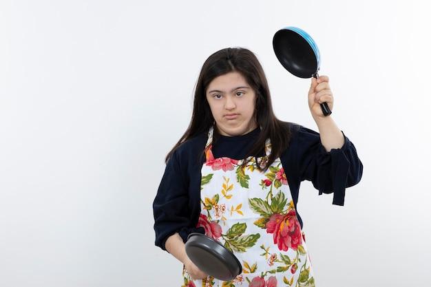 Jong meisje met het syndroom van down in schort met koekenpannen.