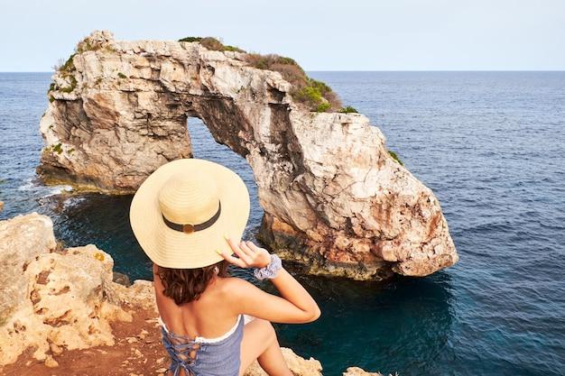 Jong meisje met hoed zitten en kijken naar de rots van es pontas in mallorca. spanje