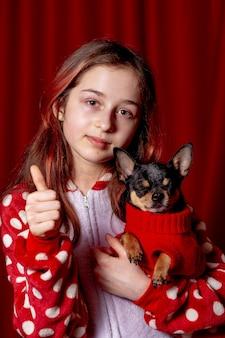 Jong meisje met hond. tienermeisje in pyjama en een chihuahua gekleed in een rode trui voor honden