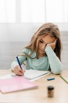 Jong meisje met hoofdpijn tijdens het doen van online lessen