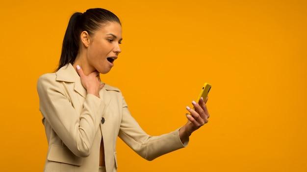 Jong meisje met huidproblemen van het gezicht poseren met een smartphone op een gele achtergrond.
