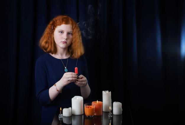 Jong meisje met kaarsen op donkerblauwe achtergrond