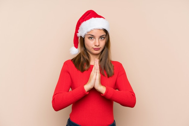 Jong meisje met kerstmishoed over het geïsoleerde muur pleiten