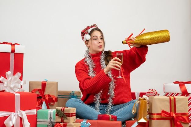 Jong meisje met kerstmuts gieten champagne rondhangen presenteert op wit