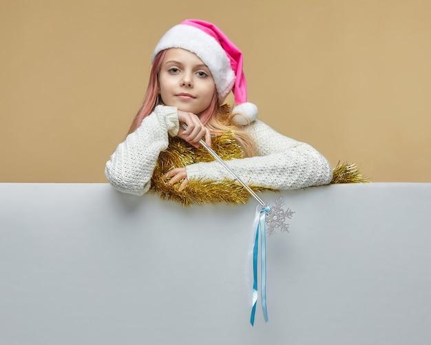 Jong meisje met klatergoud en kerstmistoverstokje