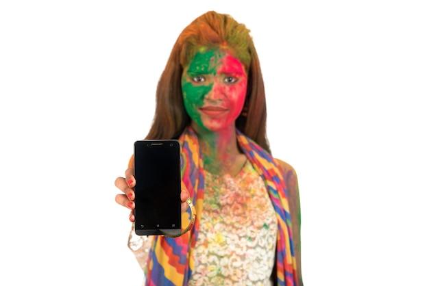 Jong meisje met kleurrijk gezicht dat het slimme telefoonscherm op holi-festival toont