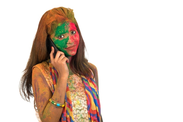 Jong meisje met kleurrijk gezicht praten aan de telefoon en festival van kleur holi vieren.