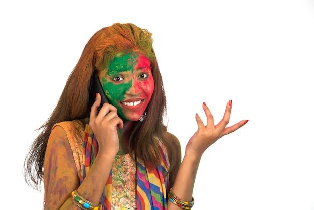 Jong meisje met kleurrijk gezicht praten over de telefoon en festival van kleur holi vieren.