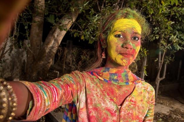 Jong meisje met kleurrijk gezicht selfie met smartphone of camera op holi-festival. festival en technologieconcept.