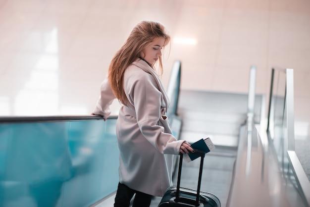Jong meisje met koffer op de roltrap.