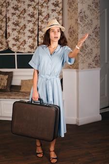 Jong meisje met koffer steekt een hand uit.