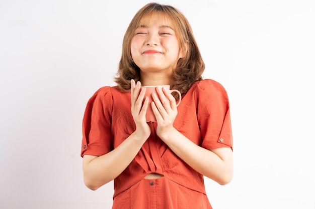 Jong meisje met koffiekopje met gelukkige uitdrukking op witte achtergrond