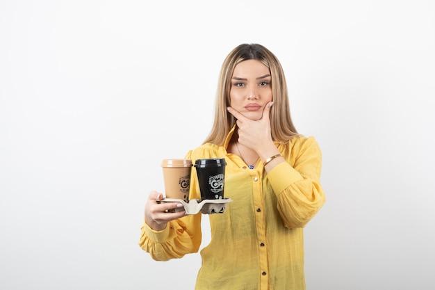 Jong meisje met kopjes koffie en denken.
