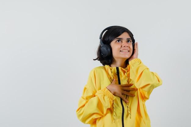Jong meisje met koptelefoon met hand, luisteren naar muziek in geel bomberjack en op zoek gelukkig