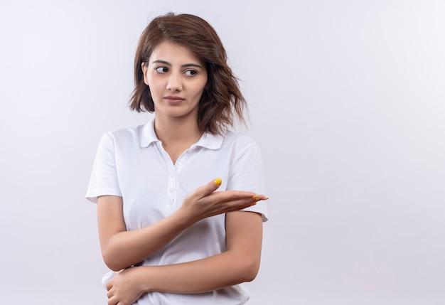Jong meisje met kort haar dat een wit poloshirt draagt dat opzij kijkt met een sceptische uitdrukking die met arm oh hand naar de zijkant wijst