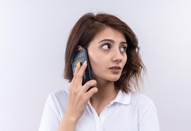 Jong meisje met kort haar dat een wit poloshirt draagt dat opzij verward kijkt terwijl het op mobiele telefoon spreekt