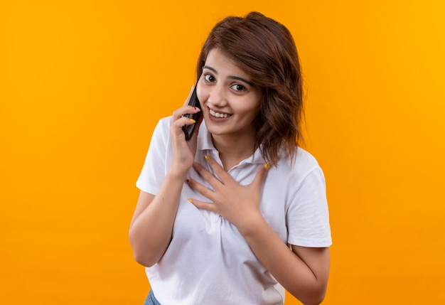 Jong meisje met kort haar dat een wit poloshirt draagt dat zich thakful en gelukkig voelt tijdens het praten op de mobiele telefoon