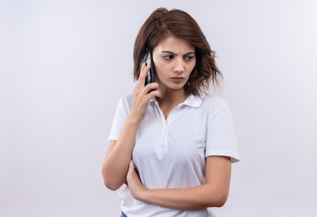 Jong meisje met kort haar dat wit poloshirt draagt dat op mobiele telefoon met fronsend gezicht spreekt
