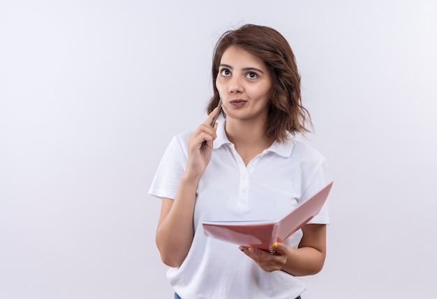 Jong meisje met kort haar die het witte notitieboekje en de pen van de poloshirt dragen die opzij met peinzende uitdrukking kijken, denken