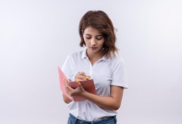 Jong meisje met kort haar die het witte notitieboekje van de poloshirt en pen dragen die met ernstig gezicht schrijven