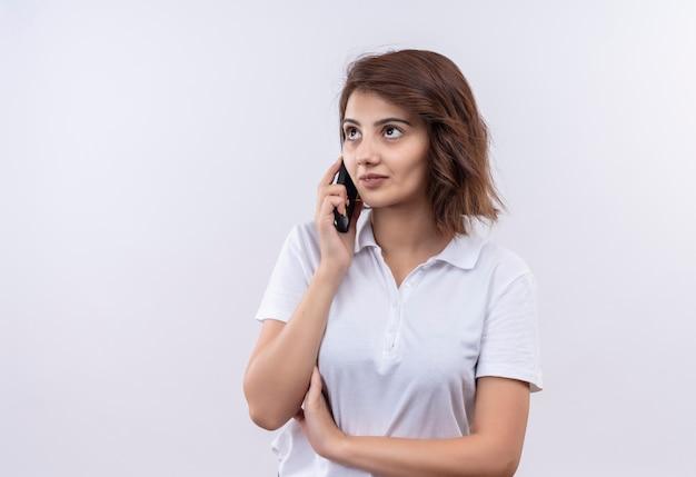 Jong meisje met kort haar, gekleed in een wit poloshirt dat zelfverzekerd kijkt tijdens het praten op de mobiele telefoon