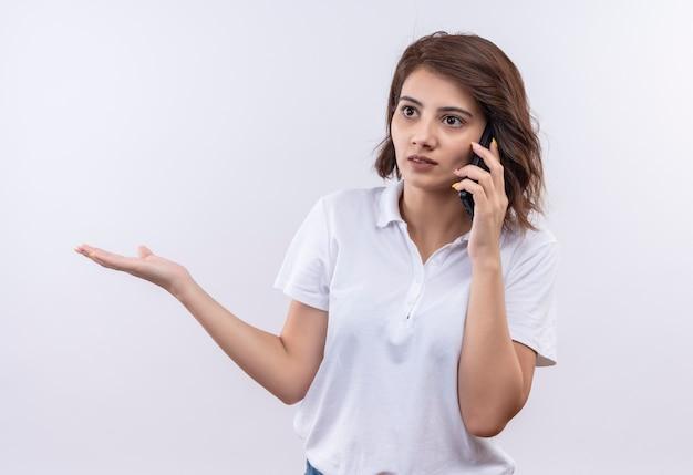 Jong meisje met kort haar, gekleed in een wit poloshirt, kijkt verward en erg angstig tijdens het praten op de mobiele telefoon