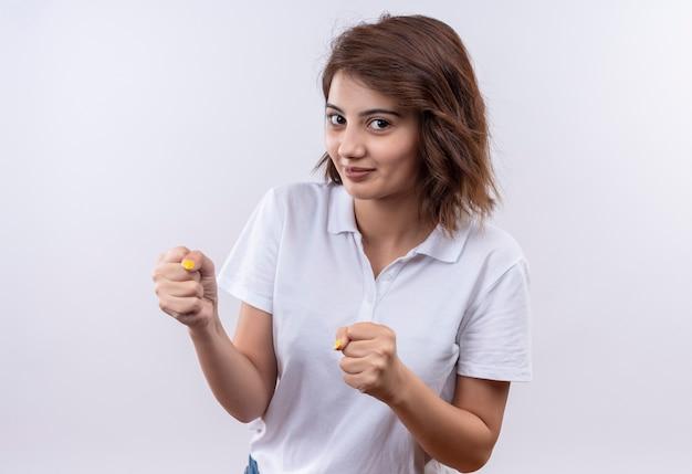 Jong meisje met kort haar, gekleed in een wit poloshirt met gebalde vuisten op zoek zelfverzekerd