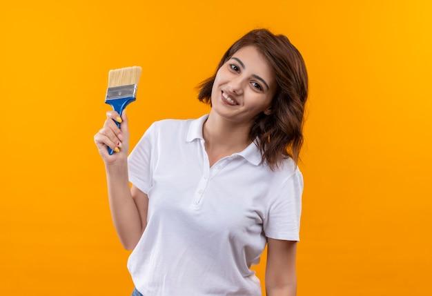 Jong meisje met kort haar, gekleed in een wit poloshirt met verfborstel glimlachend vrolijk