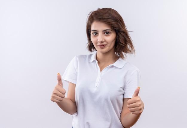 Jong meisje met kort haar, gekleed in een wit poloshirt, vriendelijk lachend opdagen met beide handen