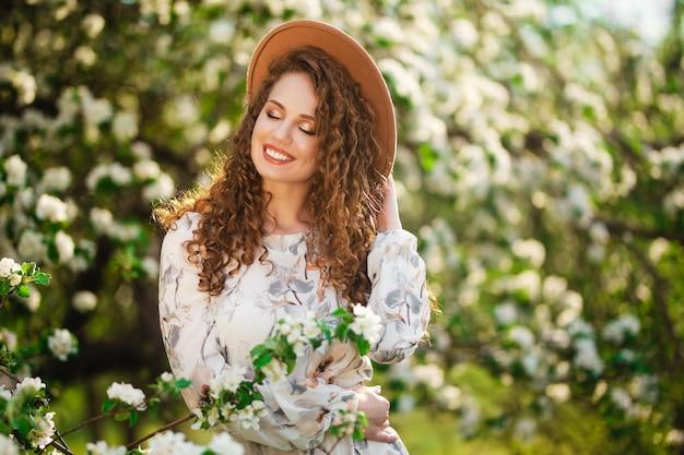 Jong meisje met krullend haar geniet van zonnige lentedag in de groene bloeiende tuin. wijfje dat lichte kleding en beige hoed draagt die gelukkig is onder witte bloesem in het park. nieuw seizoenconcept.