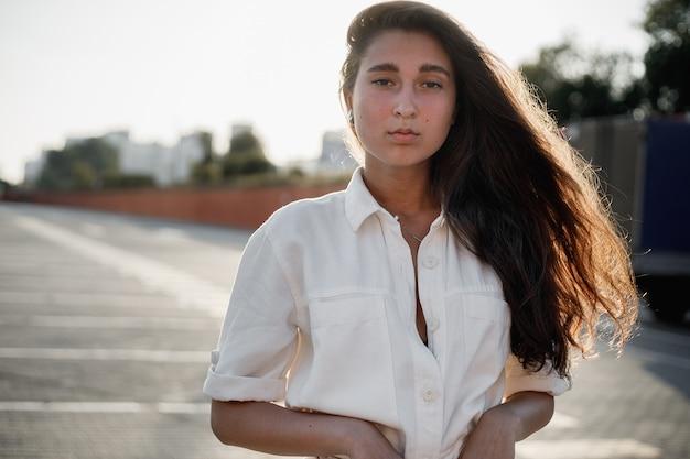 Jong meisje met lang donker haar gekleed in een wit overhemd staat op straat in de felle zon.