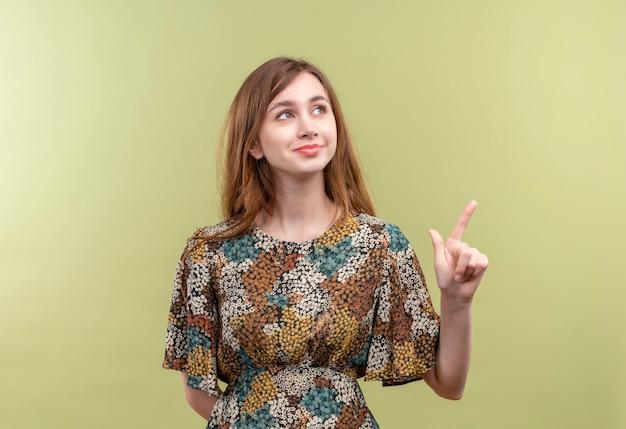 Jong meisje met lang haar dat kleurrijke kleding draagt die positief en gelukkig kijkt met omhoog wijsvinger het glimlachen