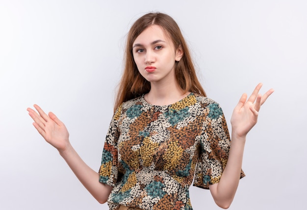 Jong meisje met lang haar dat kleurrijke kleding draagt die verward het spreiden van wapens naar de zij kijkt