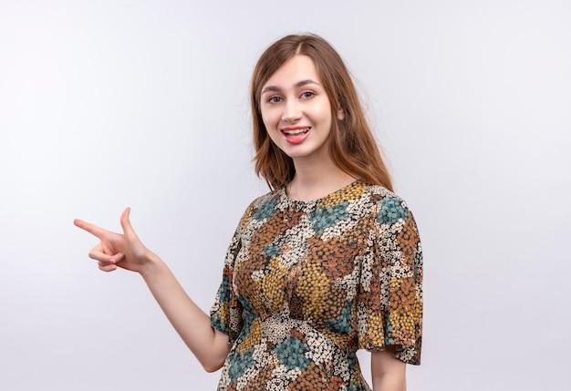 Jong meisje met lang haar dat kleurrijke kleding draagt die vreugdevol kijkt wijzend met wijsvinger aan de kant het glimlachen