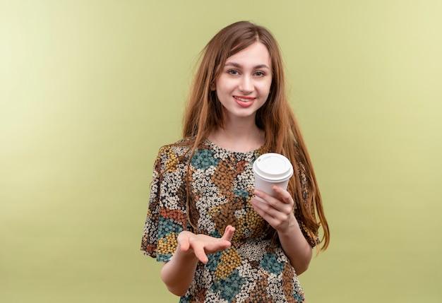 Jong meisje met lang haar die kleurrijke de koffiekop die van de kledingsholding glimlachen kijken camera bekijken die hand opheft als het stellen van vraag