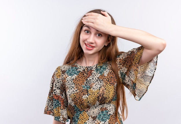 Jong meisje met lang haar dragen kleurrijke jurk camera kijken met glimlach op gezicht hoofd aan te raken met verwarren uitdrukking