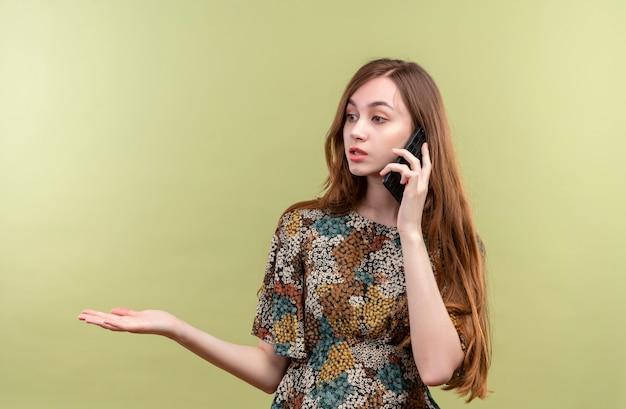 Jong meisje met lang haar, gekleed in kleurrijke jurk op zoek verward tijdens het gesprek op de mobiele telefoon