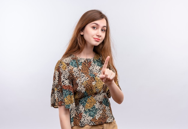 Jong meisje met lang haar, gekleed in kleurrijke jurk wijzende wijsvinger waarschuwing