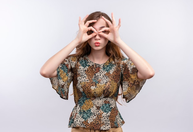 Jong meisje met lang haar, gekleed in kleurrijke kleding doet ok tekenen met vingers als een verrekijker die door de vingers kijkt