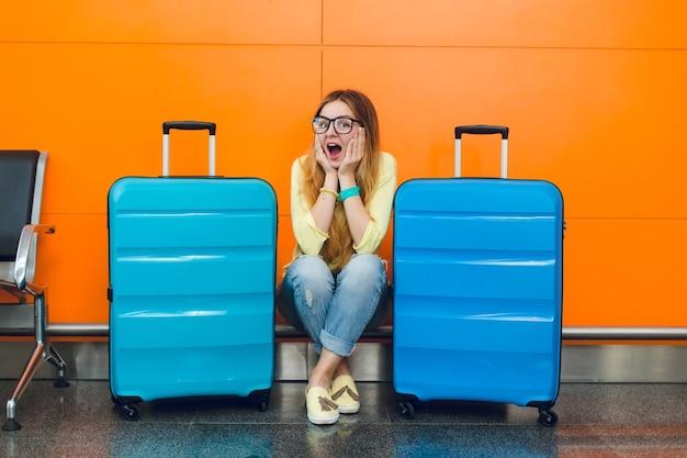 Jong meisje met lang haar in glazen zit op een oranje achtergrond tussen twee koffers. ze draagt een gele trui met een spijkerbroek. ze kijkt verbaasd naar de camera.